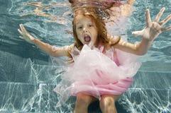 Schwimmen des kleinen Mädchens Unterwasser stockfotos