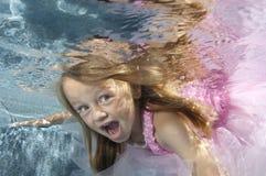 Schwimmen des kleinen Mädchens Unterwasser stockbild