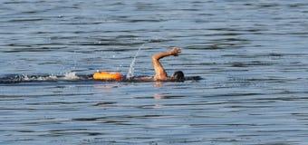 Schwimmen im offenen Wasser mit orange Schwimmaufbereitungsgerät stockbild