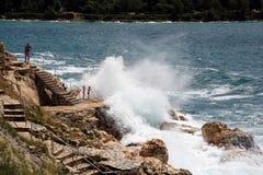 Schwimmen im Sprühen bewegt an der wilden Küste nahe Rovinj, Croati wellenartig Stockbilder