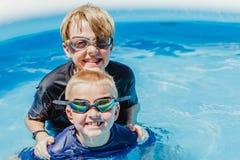 Schwimmen mit zwei Jungen in einem kleinen Pool im Sommer lizenzfreie stockfotografie