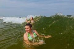 Schwimmen mit zwei Schwestern im Ozean auf Wellen Stockbild