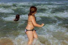 Schwimmen mit zwei Schwestern im Ozean auf Wellen Lizenzfreies Stockbild