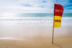 Schwimmen Sie hier Rot und gelbe Flagge auf dem Strand Stockbilder