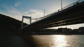 Schwimmen Sie unter der Brücke in Budapest bei Sonnenuntergang Flusskreuzfahrt, Ansicht vom sich hin- und herbewegenden touristis stock footage