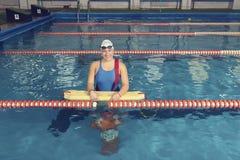 Schwimmen-Trainer in einem Pool mit Rettungs-Ausbildungsattrappe Stockfotos