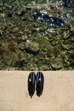 Schwimmende oder surfende Schuhe auf Strand Stockfotografie