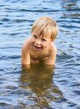 Schwimmender lachender Junge lizenzfreie stockbilder