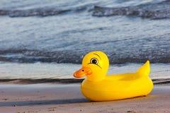 Schwimmenenten-Gummiring, Entenschwimmenring auf dem Strand Stockfotos