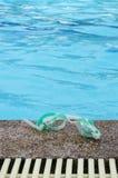 Schwimmengläser neben einem Pool Stockbilder
