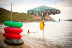 Schwimmenkreis und -sonnenschirm auf Seeküste Unschärfe stockbild