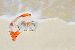 Schwimmenmaske auf dem Sand und dem Ozean Stockfotografie