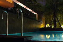 Schwimmenpoolbereich nachts mit glühender Beleuchtung des Weiche im Freien im teuren Haus in tropischem Südostasien mit flachem W Lizenzfreies Stockbild