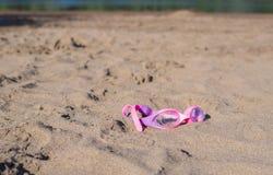 Schwimmenschutzbrillen auf Sand Stockfotos