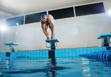 Schwimmer, der auf Startblock steht Stockfoto
