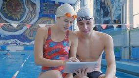 Schwimmer der männlichen und weiblichen Athleten, die eine digitale Tablette verwenden stock video footage