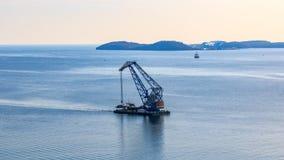Schwimmkran auf dem Hintergrund der russischen Segel der Insel durch den Bosphorus-Osten stockbild