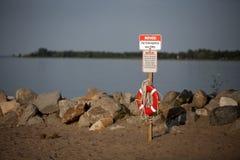 Schwimmweste-Retter-Strand-Schwimmen Rocky Shore Stockfotos