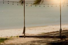 Schwingen auf dem Strand mit Sonnenuntergang stockbild