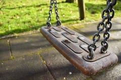 Schwingen-Schwingen-Spielplatz-verkettet altes blaues Rot-Metall Sun-Sonnenschein G stockfoto