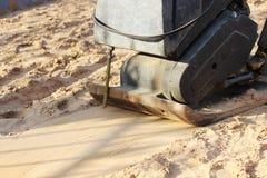 Schwingungsrolle für zusammenpressenden Sand, bevor Pflastersteine während der Reparatur des Bürgersteigs in der Stadt gelegt wer Stockfoto