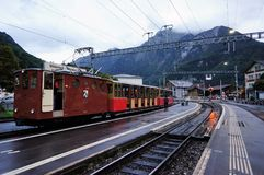 Retro train traveling from Wilderswil to Schynige platte with mist and stunning view of alpine forest as background. Jungfrau regi Stock Images