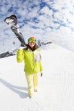 Sci andante della montagna della giovane donna sulla località di soggiorno di inverno Fotografia Stock
