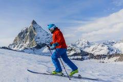 Sci che visita uomo che raggiunge la cima in alpi svizzere Immagine Stock