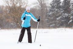 Sci di fondo della giovane donna nel parco di inverno Immagine Stock