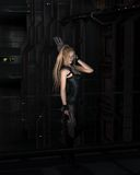 Sci-fi Heroine in a Dark City Street. Futuristic science fiction female warrior character standing in a dark city street at night, 3d digitally rendered Stock Photos