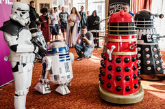 Sci-Fi Scarborough attendees. Scarborough, UK - April 08, 2017: People dressed as a `Stormtrooper` and `Daleks` encounter an R2-D2 model at Sci-Fi Scarborough Stock Photography