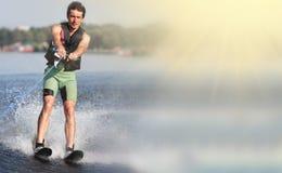Sci nautici di guida dell'uomo del primo piano sul lago di estate al giorno soleggiato Sport attivo dell'acqua Spazio per testo immagine stock