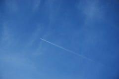 Scia dell'aeroplano contro chiaro cielo blu Immagini Stock
