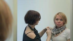 Sciarpa blu bianca dei legami dello stilista bella al cliente nel negozio di modo stock footage