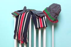 Sciarpa maschio e guanti del cappello che si asciugano su un radiatore fotografia stock