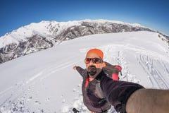 Sciatore adulto del alpin con la barba, gli occhiali da sole ed il cappello, prendenti selfie sul pendio nevoso nelle belle alpi  Immagini Stock