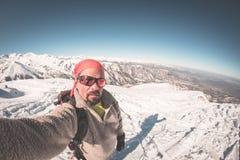 Sciatore adulto del alpin con la barba, gli occhiali da sole ed il cappello, prendenti selfie sul pendio nevoso nelle belle alpi  Fotografie Stock
