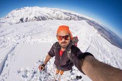 Sciatore adulto del alpin con la barba, gli occhiali da sole ed il cappello, prendenti selfie sul pendio nevoso nelle belle alpi  Fotografia Stock Libera da Diritti