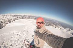 Sciatore adulto del alpin con la barba, gli occhiali da sole ed il cappello, prendenti selfie sul pendio nevoso nelle belle alpi  Fotografie Stock Libere da Diritti