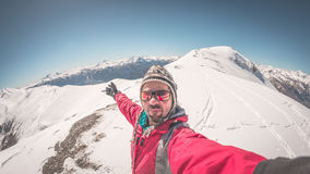 Sciatore adulto del alpin con la barba, gli occhiali da sole ed il cappello, prendenti selfie sul pendio nevoso nelle belle alpi  Fotografia Stock