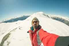 Sciatore adulto del alpin con la barba, gli occhiali da sole ed il cappello, prendenti selfie sul pendio nevoso nelle belle alpi  Immagine Stock