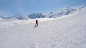 Sciatore alpino della donna elegante che scia giù il pendio in montagne archivi video