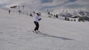 Sciatore attivo che scia giù dai pendii di montagna nell'inverno sullo sci alpino stock footage