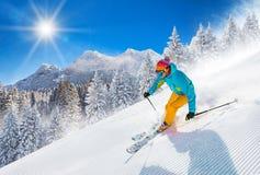 Sciatore che scia in discesa in alte montagne immagini stock