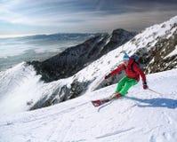 Sciatore che scia in discesa in alte montagne Immagine Stock