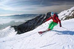 Sciatore che scia in discesa in alte montagne Fotografia Stock
