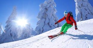 Sciatore che scia in discesa in alte montagne Fotografia Stock Libera da Diritti
