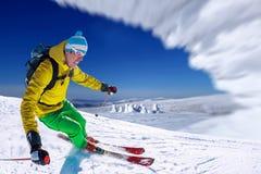 Sciatore che scia in discesa in alte montagne Fotografie Stock Libere da Diritti