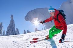 Sciatore che scia in discesa in alte montagne contro il cielo blu Immagini Stock Libere da Diritti