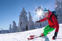 Sciatore che scia in discesa in alte montagne contro il cielo blu Fotografie Stock